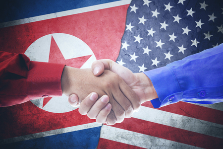 Hands of two businessmen shaking hands with North Korea and USA flag in the background