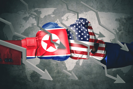 Concept of conflict. Two boxing gloves with North Korea and USA flag, declining arrows Stock Photo