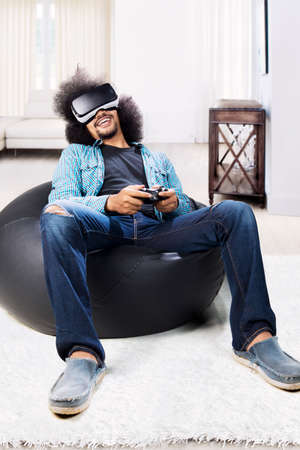 African man is playing a video game with virtual reality glasses and a joystick in the living room Stock Photo