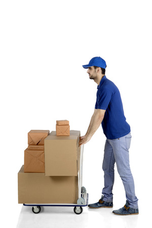 Portrait of Caucasian man courier pushing packages on the trolley, isolated on white background