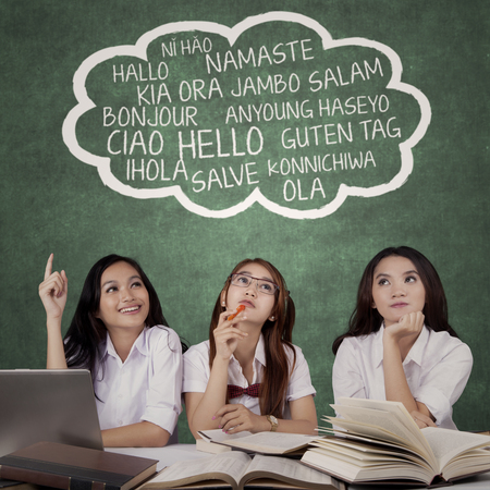 Three female high school students learn different languages in the classroom with books on table and looking at speech bubble Stock Photo