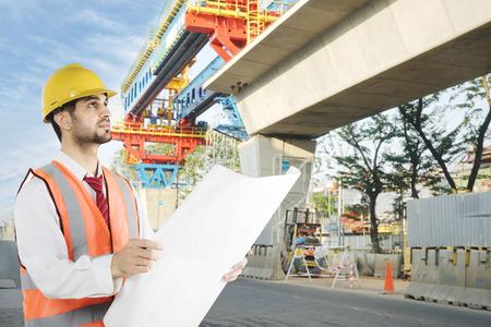 Immagine dell'avvocato italiano che controlla nel cantiere mentre lavora con un disegno Archivio Fotografico - 86799983