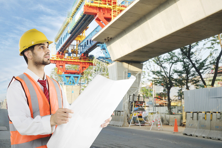Picture of Italian foreman checking in the construction site while working with a blueprint Stok Fotoğraf