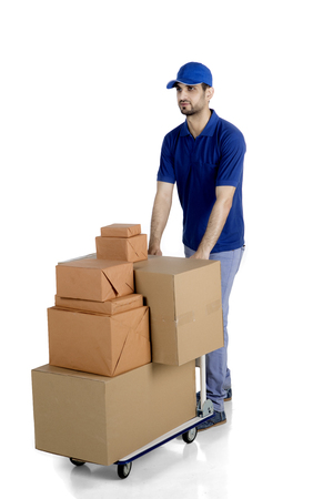 Picture of Arabian courier wearing uniform while carrying boxes with trolley, isolated on white background