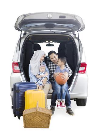흰색 배경에 고립 된 자동차의 트렁크에 함께 앉아있는 동안 그의 부모와 함께 말하기 어린 소년
