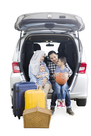 Little boy speaking with his parents while sitting together in the trunk of a car, isolated on white background Stockfoto