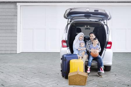 집 차고에서 자녀와 함께 자동차 트렁크에 앉아있는 동안 여행을 준비 무슬림 부모님의 그림 스톡 콘텐츠