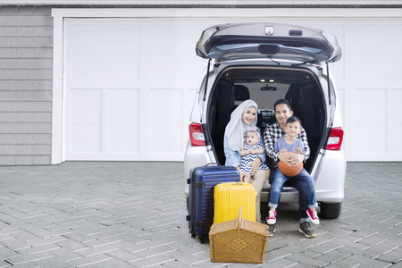 Picture of Muslim parents ready to road trip while sitting in the car trunk with their children in the house garage
