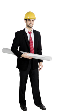 Full length of a successful bearded architect standing in the studio while wearing formal suit and holding blueprint