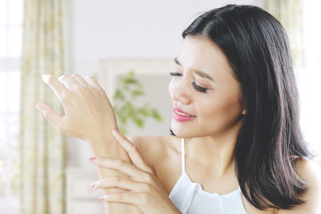 Beauty concept. Pretty woman caressing her arm skin healthy while sitting in the bedroom Stock Photo