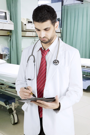 Portrait of an Arabian man doctor writing on the clipboard while standing in the patient room