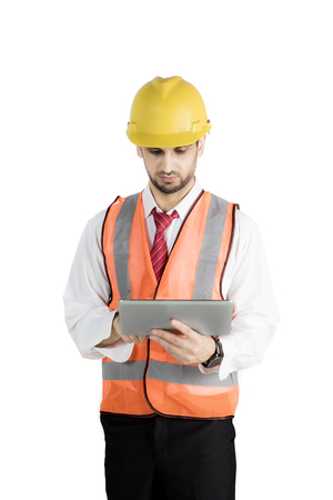 Male engineer using a digital tablet computer in the studio while wearing helmet and orange safety vest Stock Photo