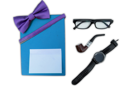 Top view of gift box with a blank sticky note near an eyeglasses, smoke pipe, and wristwatch, isolated on white background Stock Photo