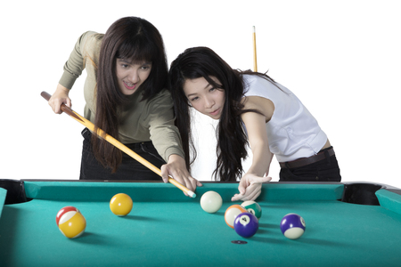 Portrait of two beautiful multiethnic girls playing billiards together, isolated on white background
