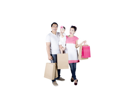 Full length of young Asian family looks happy while shopping together in the studio, isolated on white background Stock Photo