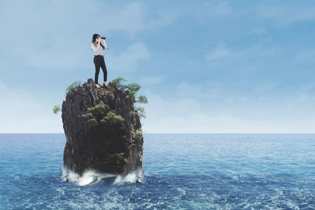 Young businesswoman standing on coral reef at sea while looking through binoculars Reklamní fotografie