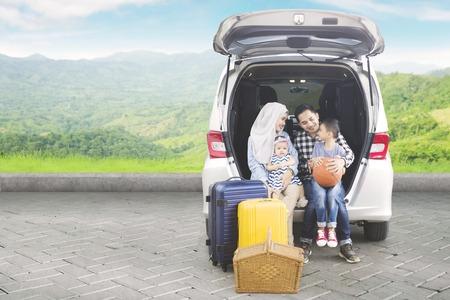산에서 여행하는 동안 자동차 트렁크에 함께 앉아 아시아 가족의 그림