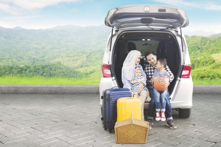 Picture of Asian family sitting together in the car trunk while traveling in the mountain