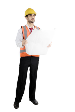 Full length of handsome architect holding blueprints and looking at copyspace while wearing helmet and safety vest