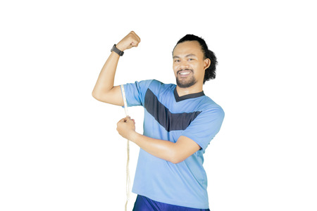 Picture of Afro man measuring his bicep with measure tape, isolated on white background