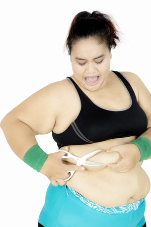 Overweight woman wearing sportswear and using a scissors for cutting fat on her belly, isolated on white background Reklamní fotografie - 87257458