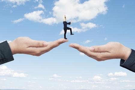 Hombre de negocios desconocido con la cabeza de cartón encontrando un camino mientras camina dos manos que ayudan