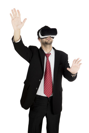 Portrait of young businessman using a virtual reality goggles while standing in the studio Stock Photo