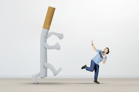 Picture of African man chased by a cigarette while running in the studio, isolated on white background