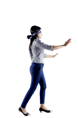 Portrait of young businesswoman blindfolded with a tie while walking in the studio, isolated on white background Banco de Imagens