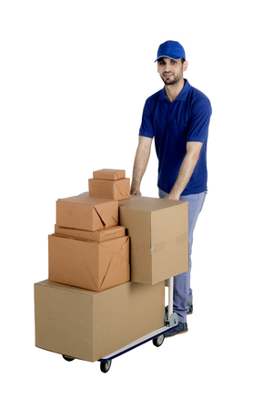 Portrait of Italian postman looking at the camera while pushing a trolley of packages in the studio