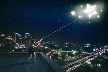 Beautiful businesswoman standing on the rooftop while pulling a bright star in the night sky
