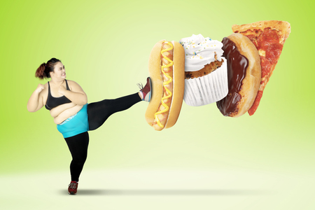Diet concept. Overweight woman avoids to eat junk foods by kicking a hot dog, cupcake, donut, and pizza