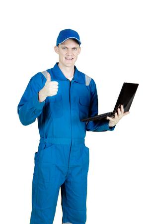 Meccanico maschio europeo che sta nello studio mentre mostrando pollice su e tenendo un computer portatile