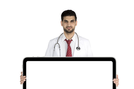 Italian male doctor standing in the studio while showing a blank billboard, isolated on white background