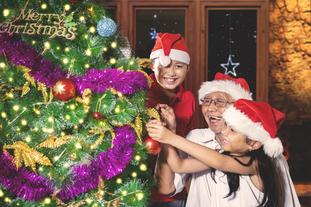 Happy grandfather and his grandchildren decorating a Christmas tree while wearing Santa hat at home