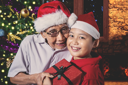 Cute little boy giving a Christmas gift to his grandfather while wearing Santa hat and smiling at the camera near a Christmas tree at home Stock Photo