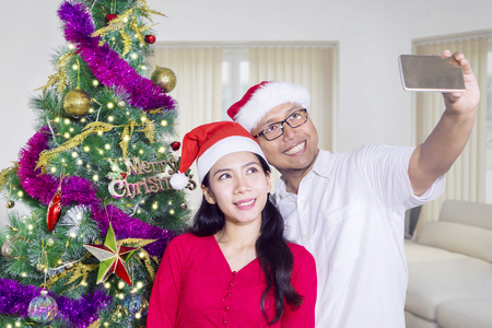 Young couple taking selfie photo while wearing Santa hat near a Christmas tree at home Stock Photo