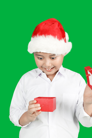Portrait of amazed little boy opens a Christmas gift box while wearing a Santa hat in front of green screen background