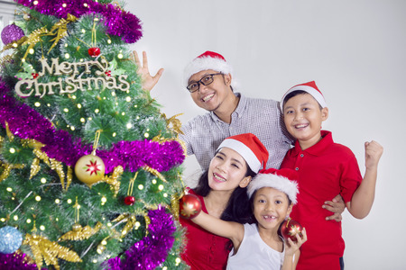Asian family smiling at the camera near a Christmas tree while celebrating Christmas in the studio Stock Photo