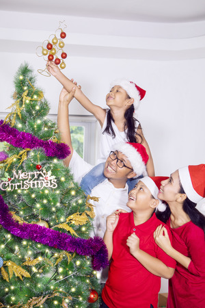 Portrait of Asian family putting a Christmas ornament on the Christmas tree. Shot at home Banco de Imagens