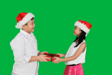 Photo of a cute little boy giving a Christmas gift to his sister while wearing Santa hat and standing in front of green screen background Stock Photo