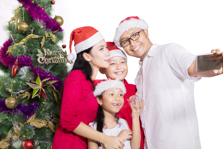 Happy family standing near a Christmas tree and taking selfie photo while wearing Santa hat, isolated on white background