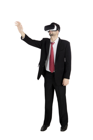 Portrait of young businessman touching something while wearing virtual reality goggles in the studio