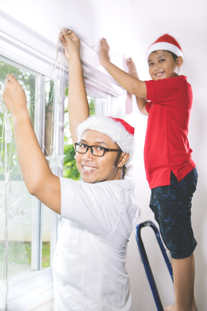 Happy young father and his son preparing Christmas day while wearing Christmas hat and put Christmas light on the wall Standard-Bild