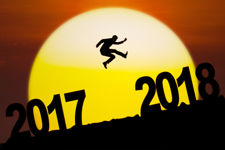 Silhouette of young businessman jumping between numbers 2017 to 2018 with sundown on the mountain