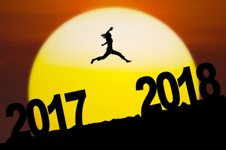 Picture of an unknown woman leaping between numbers 2017 to 2018 with sundown on the mountain