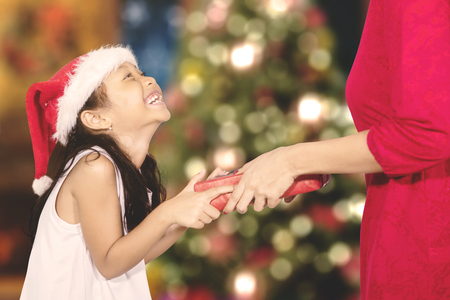 Portrait of a cheerful little girl giving a Christmas gift to her mother while wearing Santa hat with bokeh Christmas tree background