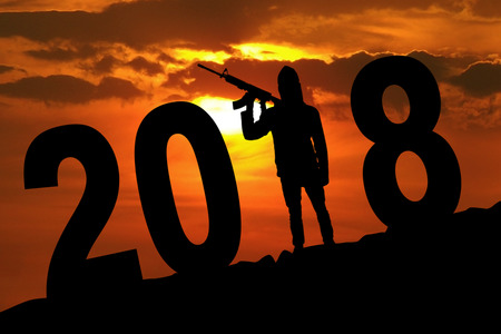 Silhouette of male terrorist holding a weapon while standing with numbers 2018 on the hill