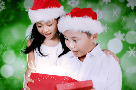 Portrait of two surprised children open a Christmas present together while wearing Santa hat with bokeh light background