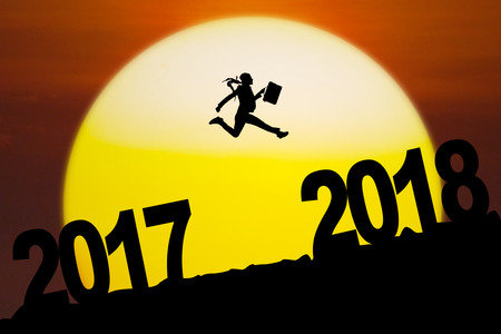 Silhouette of young businesswoman carrying a suitcase while leaping between numbers 2017 to 2018 with sundown Stock Photo